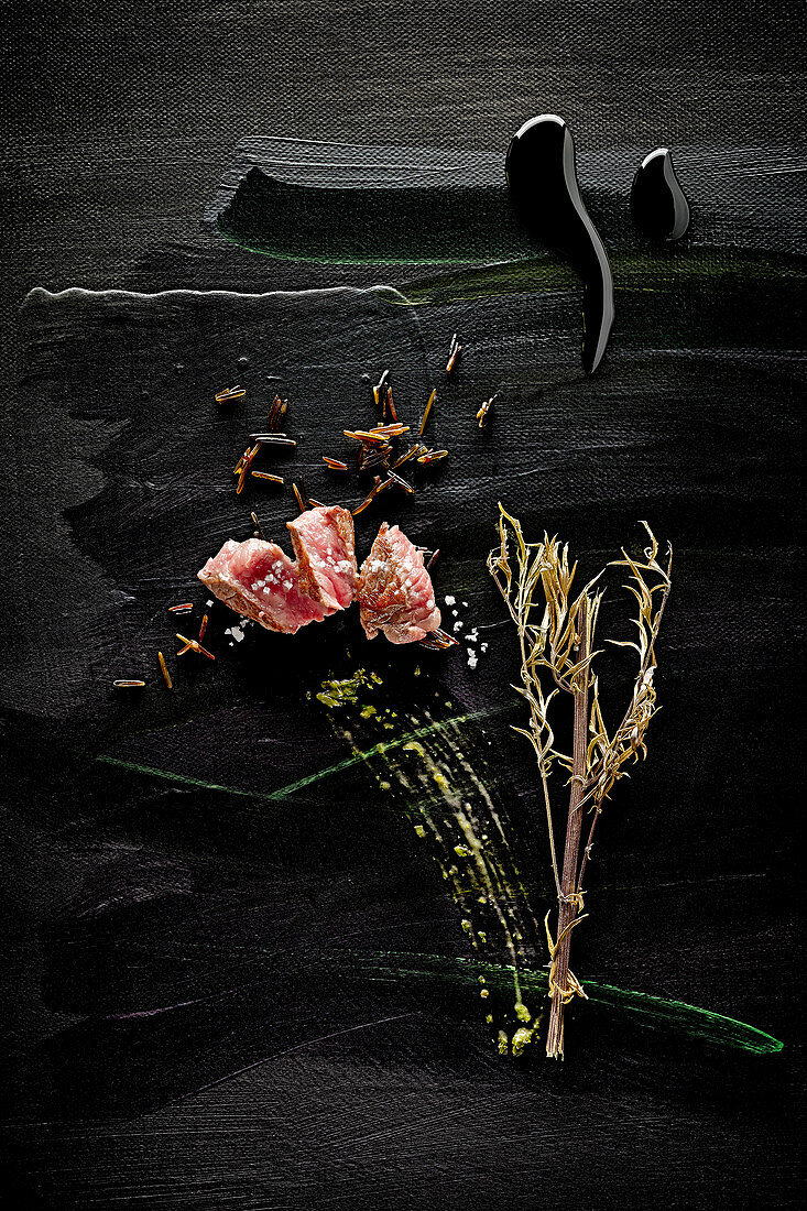 Food art: beef with black rice, comfrey and pesto on a black surface