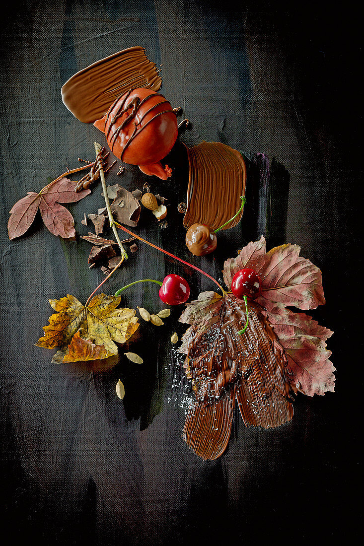 Food art: winter apples with chocolate, cherries and autumnal leaves on a black surface