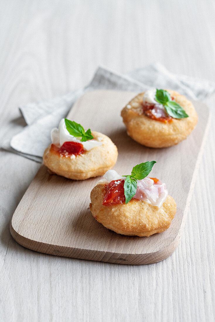 Montanarine con pomodorini, lardo e pecorino (fried mini pizzas, Italy)