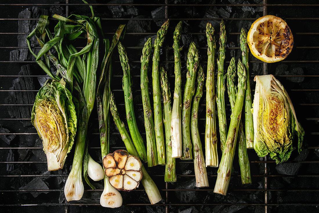 Grilled vegetables green asparagus, garlic, lemon, spring onion, salad on bbq grill rack over charcoal