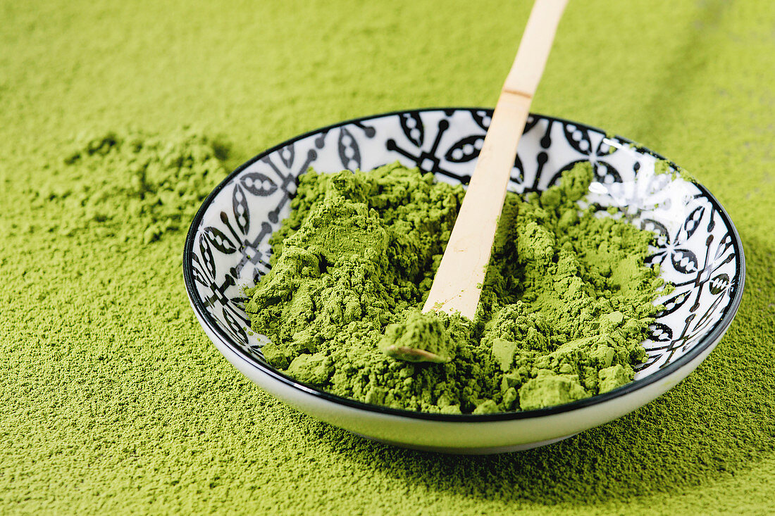 Green tea matcha powder in ceramic bowl with traditional bamboo spoon over powdering matcha as background