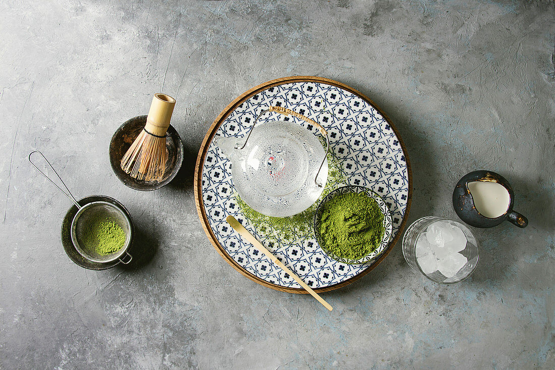 Ingredients for making matcha ice drink: Green tea matcha powder in ceramic bowl, traditional bamboo spoon, whisk on plate, glass teapot, ice cubes
