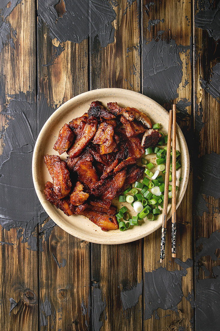 Chinese traditional dish Cantonese BBQ Pork Belly with spring onion served in ceramic plate with chopsticks over dark wooden plank background