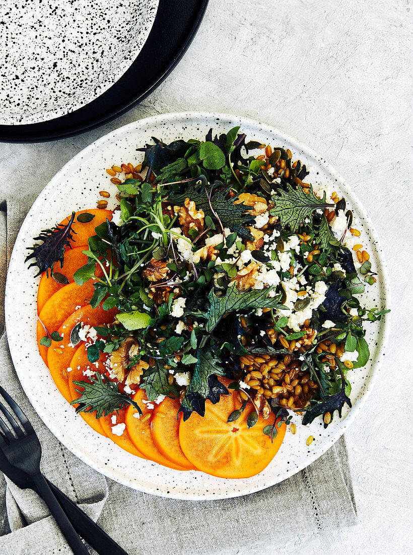 Healthy persimmon and farro salad with kale, watercress, goat cheese and nuts