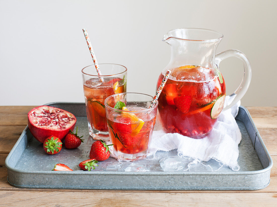 Pomegranate Pimms in jug with fruit on metal tray
