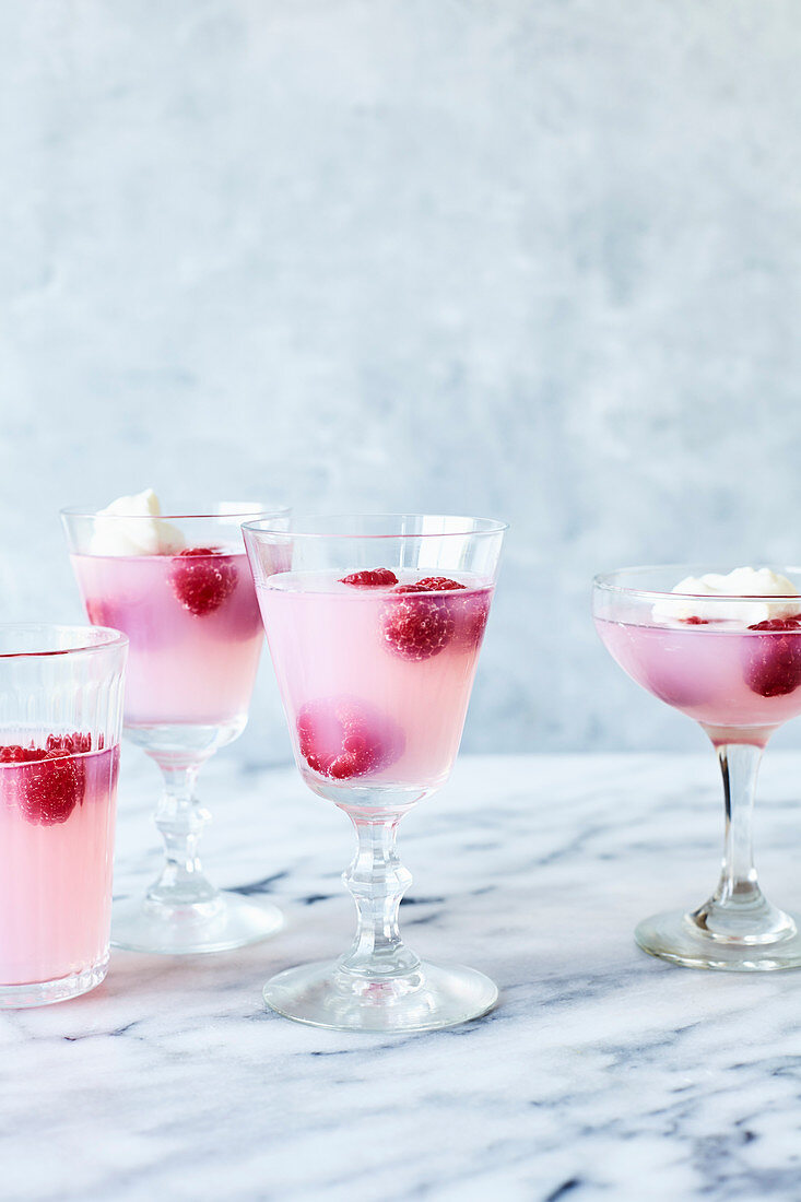 Pink lemonade jelly with raspberries and cream on light marble background
