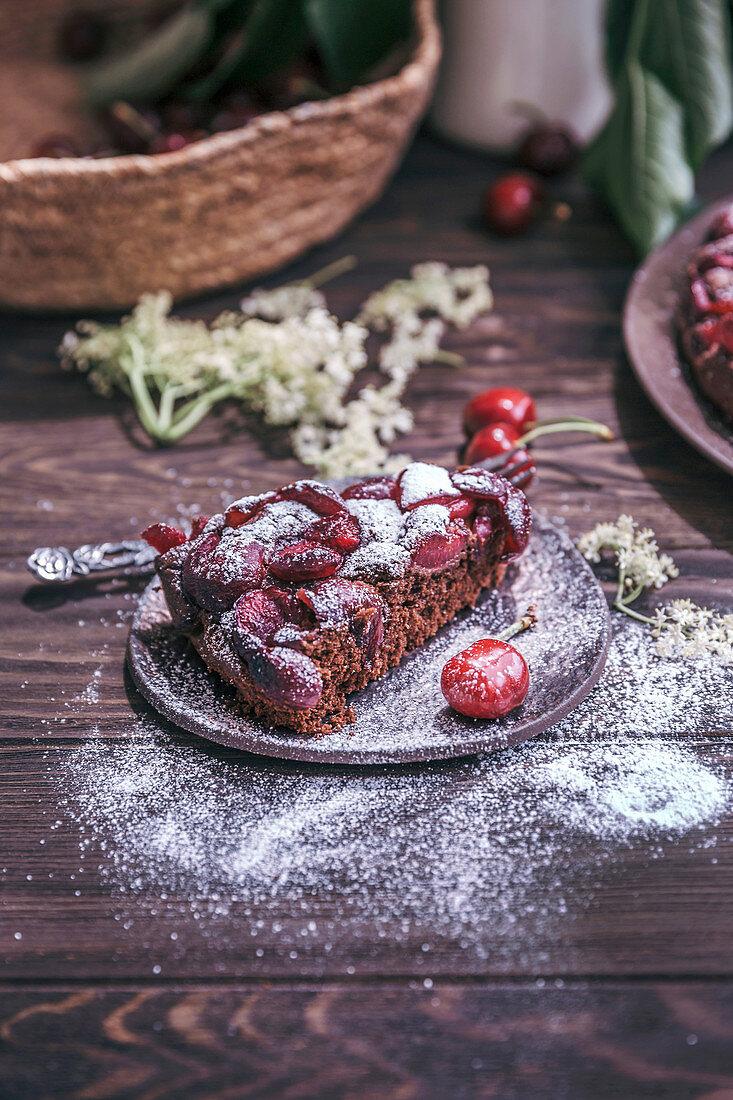 Slice old cherry chocolate cake on a dessert plate