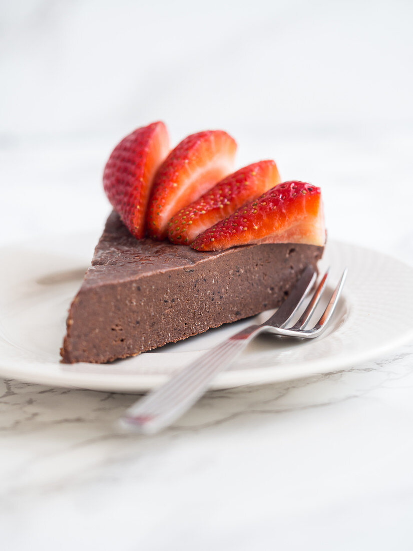 Slice of a flourless chocolate fudge cake with strawberries (vegan and paleo)