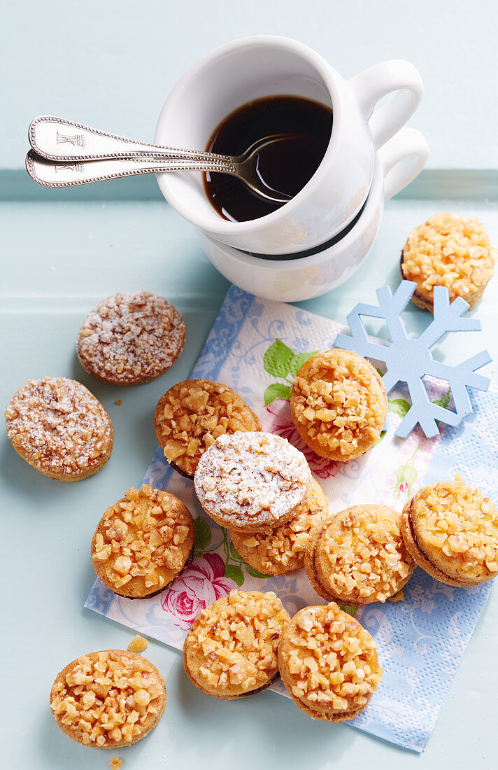 Small crunchy cookies filled with elderberry jam, served with a cup of coffee
