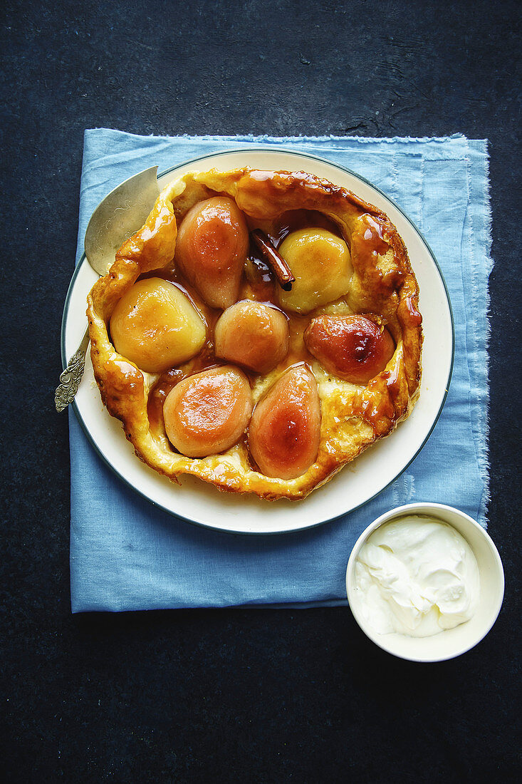 Overhead shot of tart tatin with pears and whipped cream on dark blue background