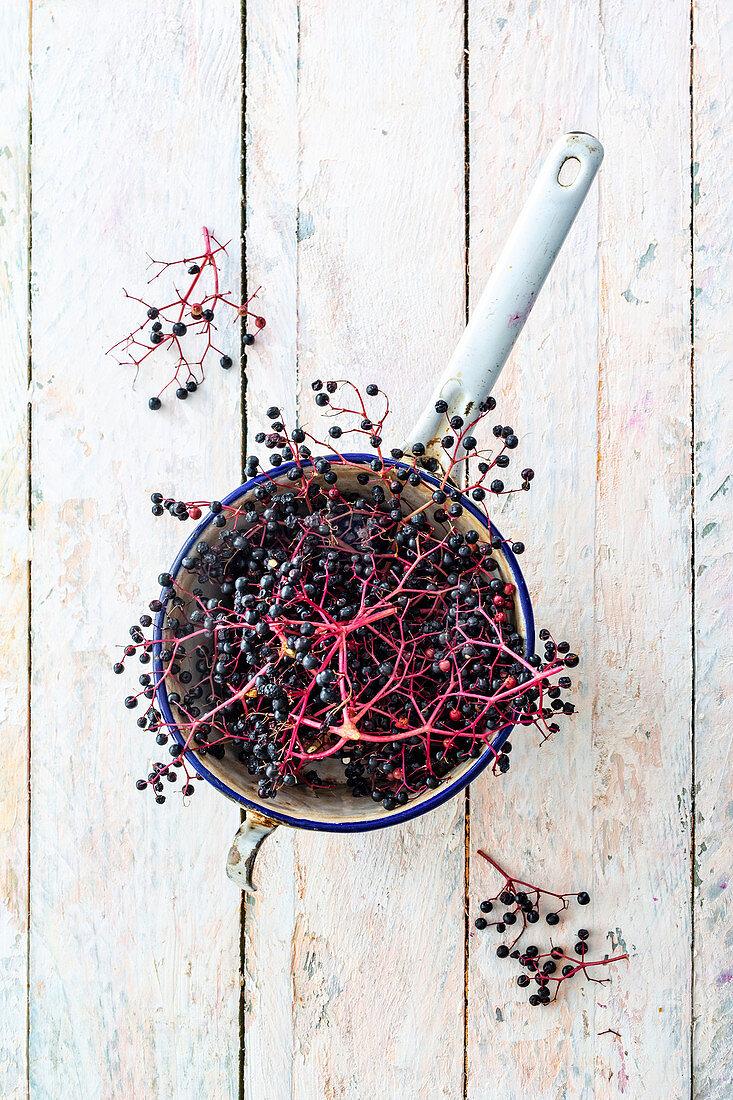 Elderberries in an enamel sieve