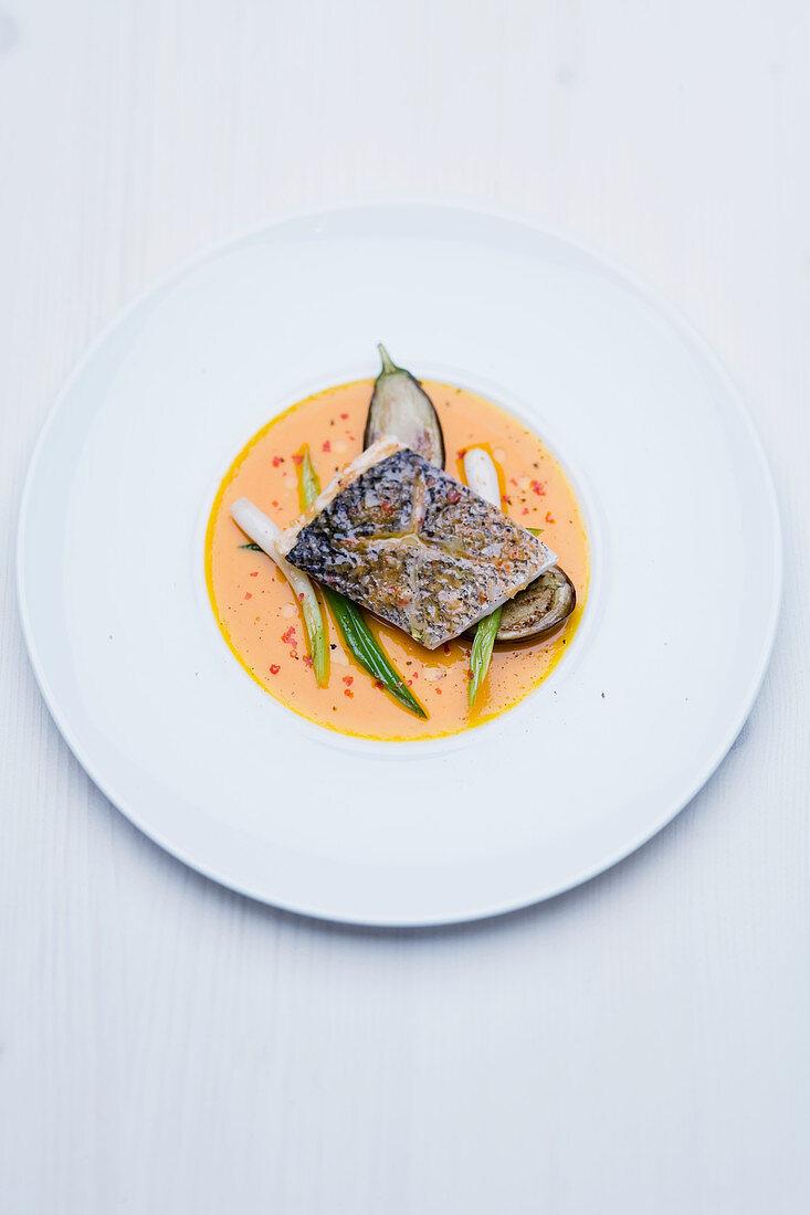 Sea bass fillet with lemon grass and ginger flowers, roasted aubergines and spicy pumpkin sauce