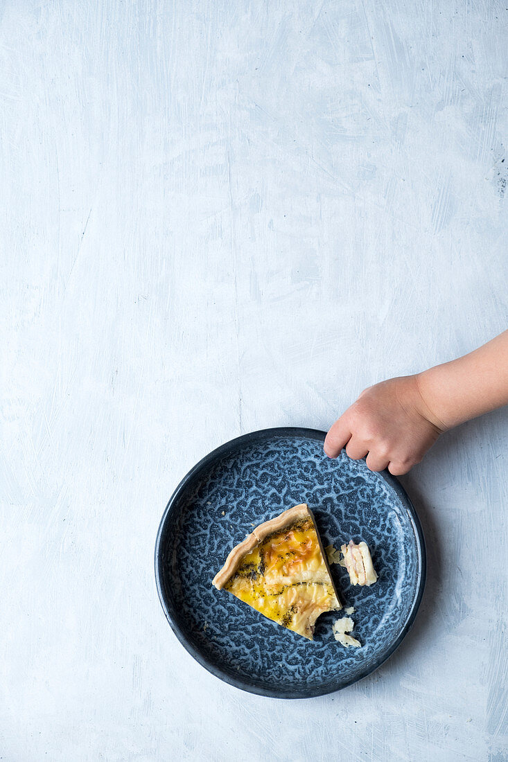 A plate with a piece of quiche with a little child hand on a white surface