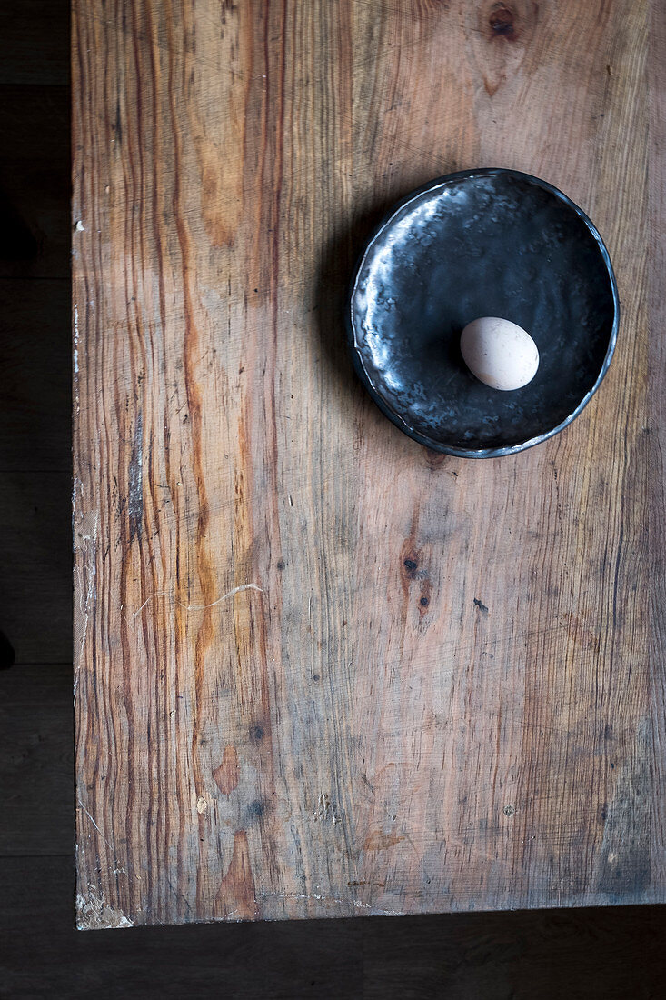 Only one egg on a black plate at a wooden table