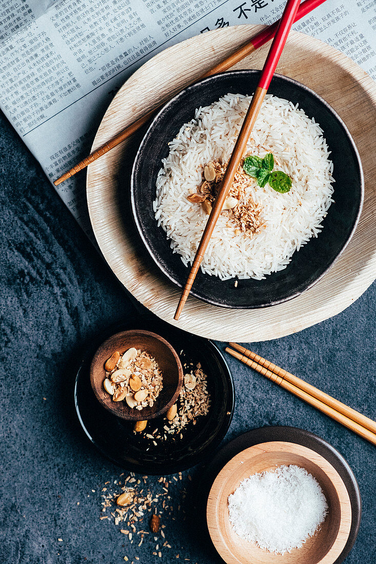 A boewl filled with rice and wooden sticks, cocos and peanuts in a bowl with a Japanese newspaper at a dark backdrop