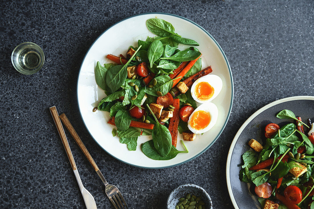 Fresh salad with fried cheese, roasted carrot, cherry tomatoes and pumpkin seeds