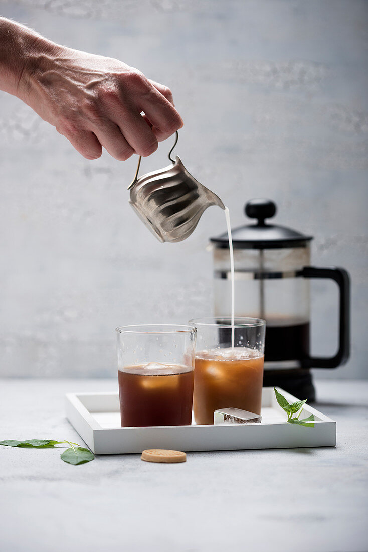 A woman pouring almond milk into iced cold brew coffee