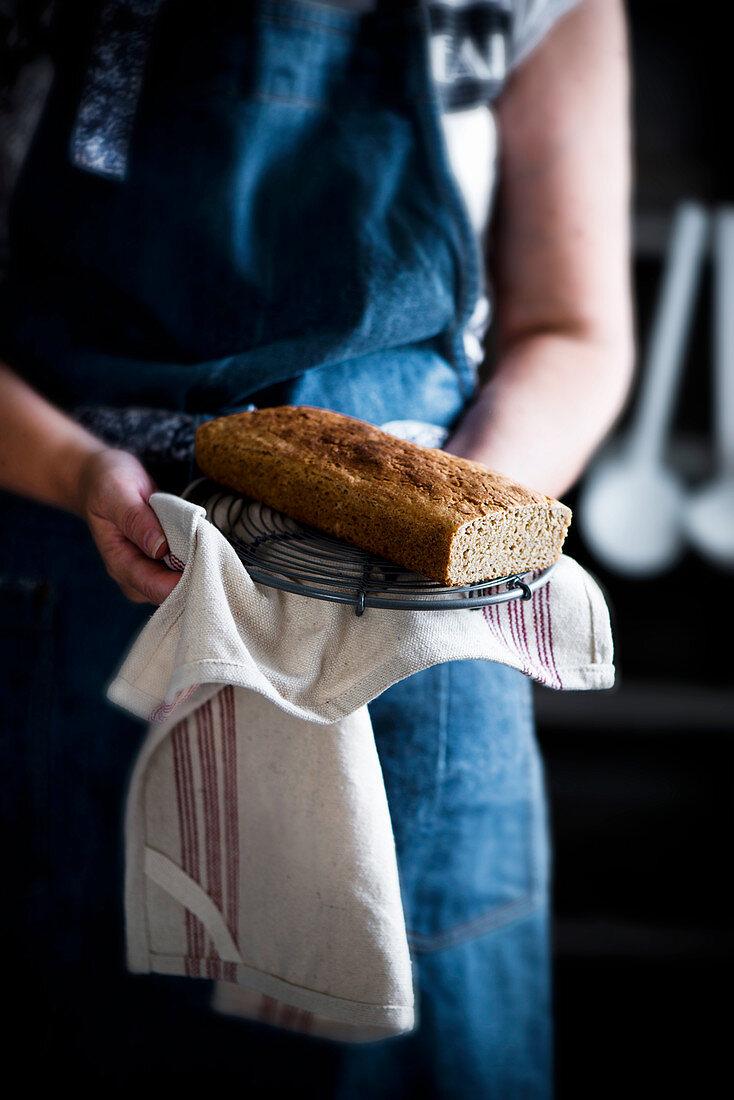 Frau präsentiert selbstgemachten Kuchen auf Geschirrtuch