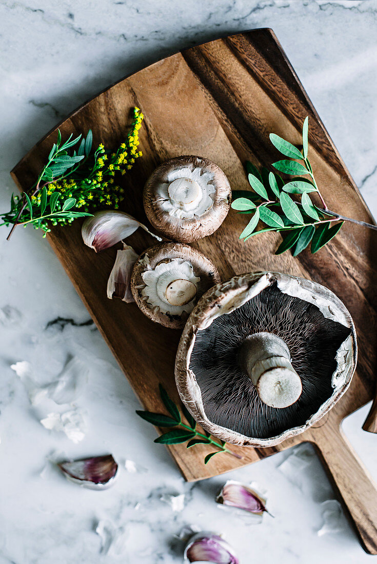 Fresh brown mushrooms on wooden board on kitchen