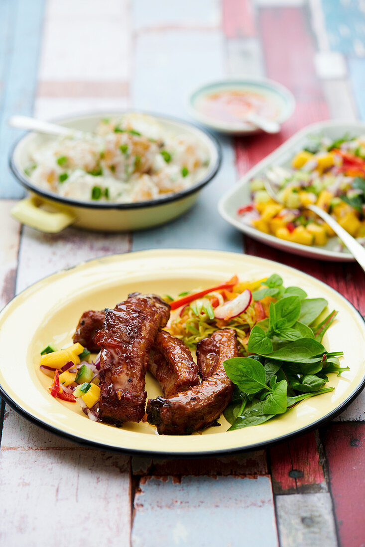 Marinated BBQ lamb ribs with mango cucumber salad