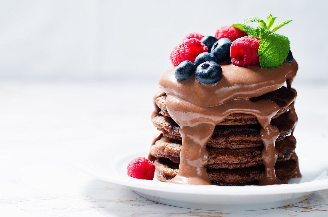 Chocolate pancake with blueberries, raspberies and chocolate sauce