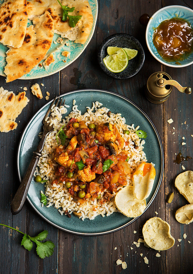 Vegan cauliflower curry, served with brown rice on a blue plate with nan bread, popadoms and mango chutney