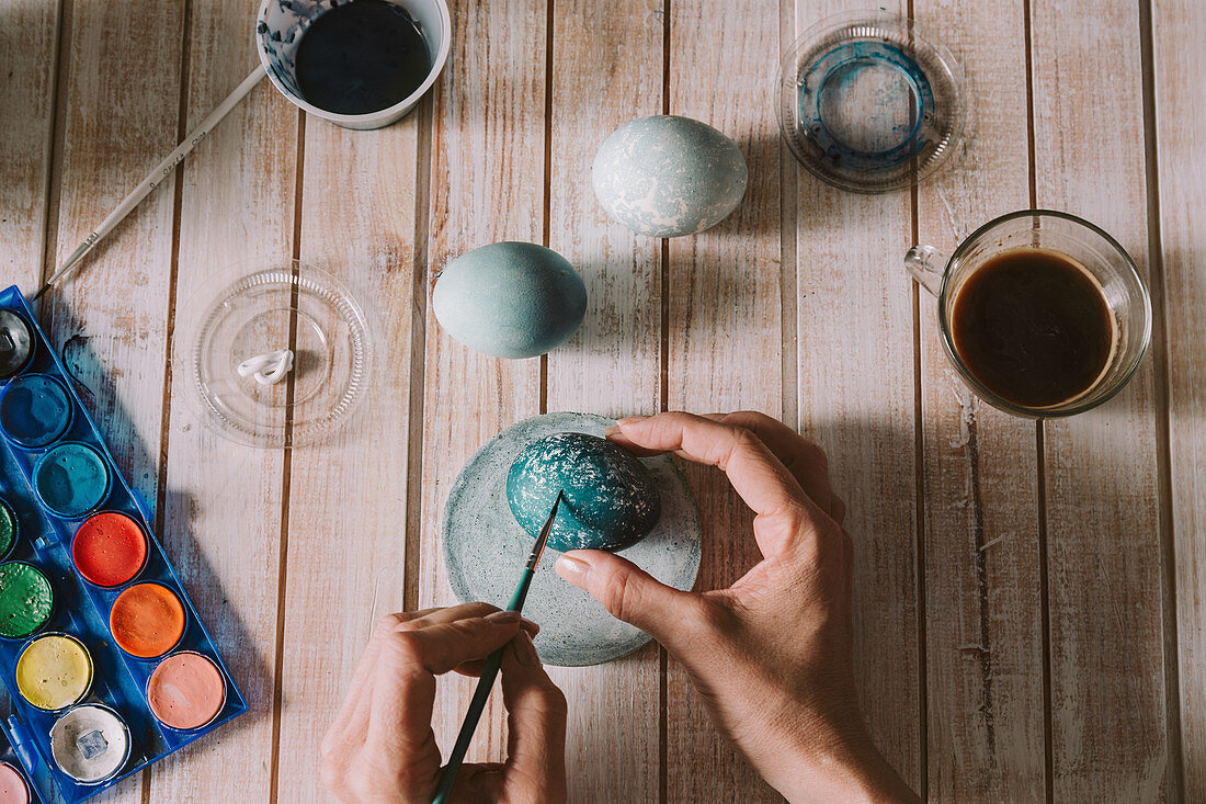 Hands of person painting the egg decoration for easter