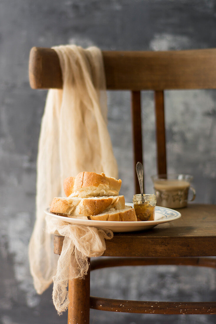 Yeast bun with jam on a chair in a country style