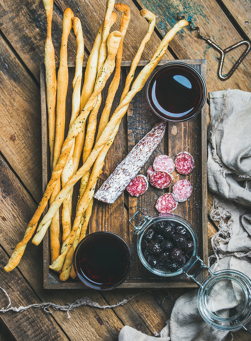 Italian Grissini bread sticks, dry cured pork meat sausage, black olives in jar and red wine in glasses