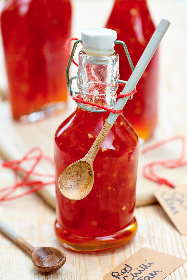 Red chili jam in a bottle with a wooden spoon for gifting