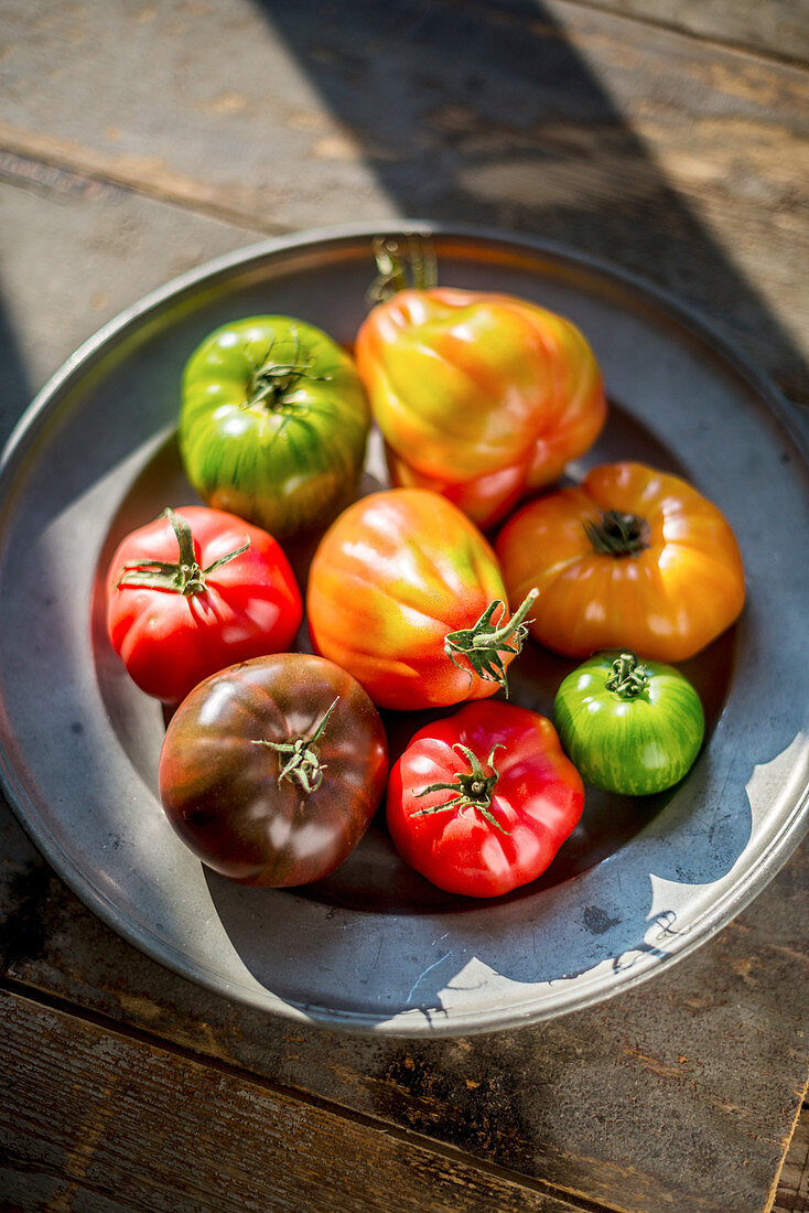 Various coloured tomatoes on a pewter plate