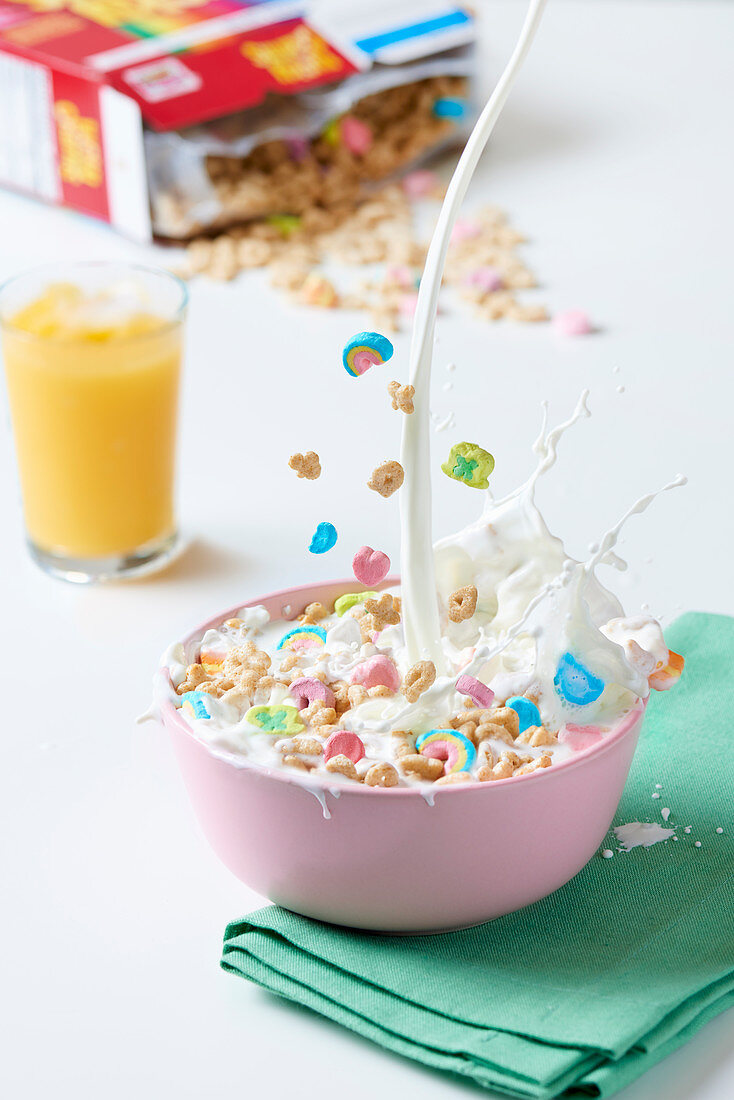 Milk being poured into a bowl of colourful cereal