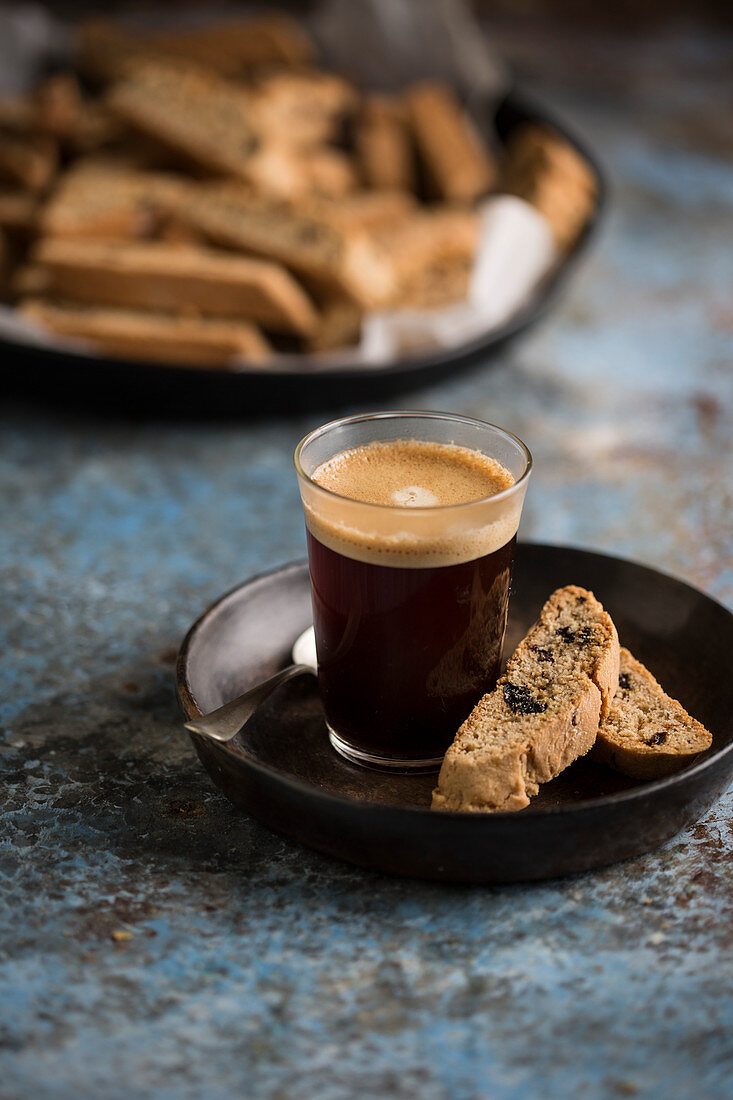 An espresso served in a glass with two biscotti