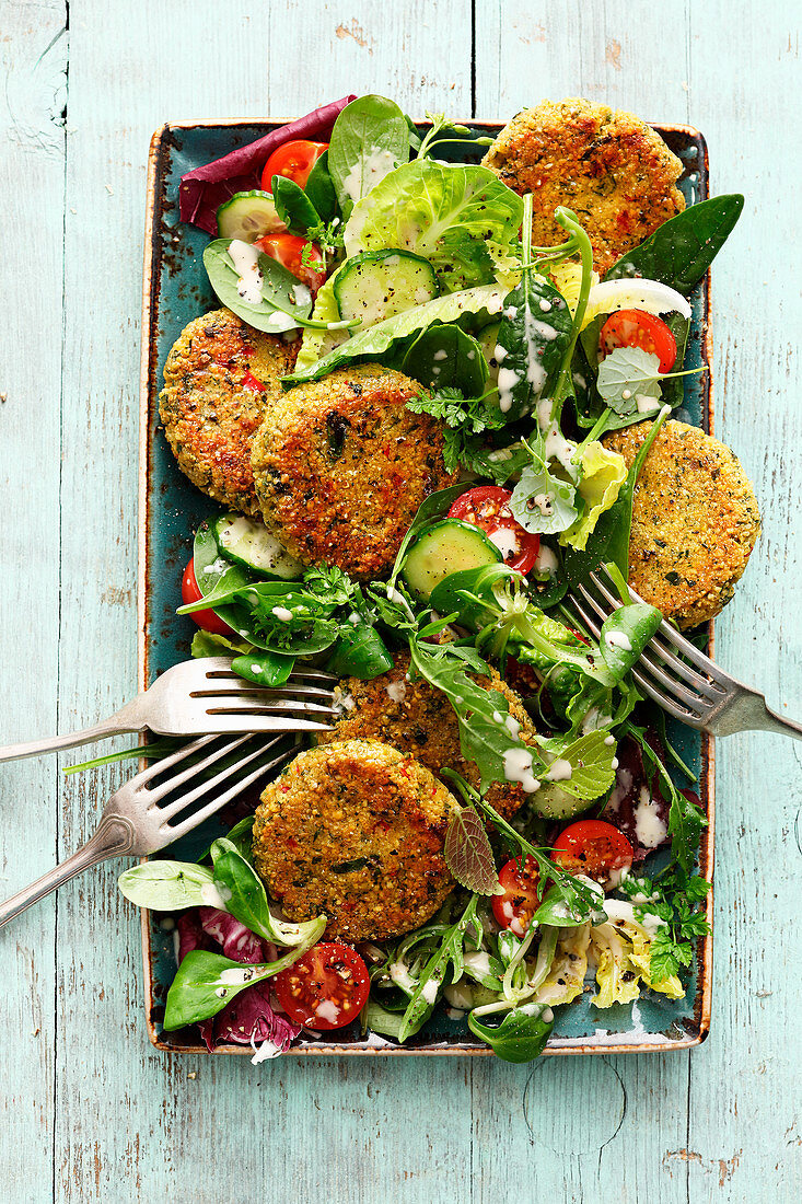 A colourful salad with falafel rounds and tahini sauce