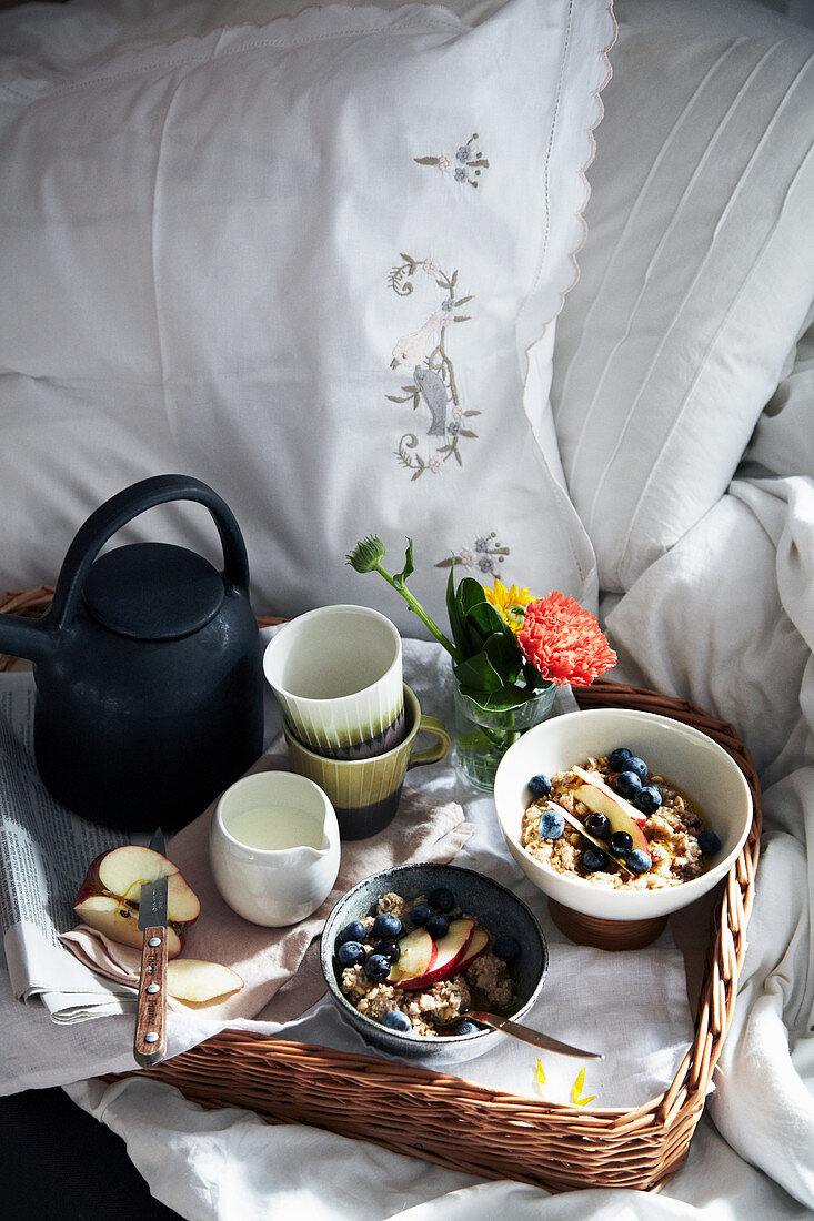 A breakfast tray with muesli, milk and tea in bed