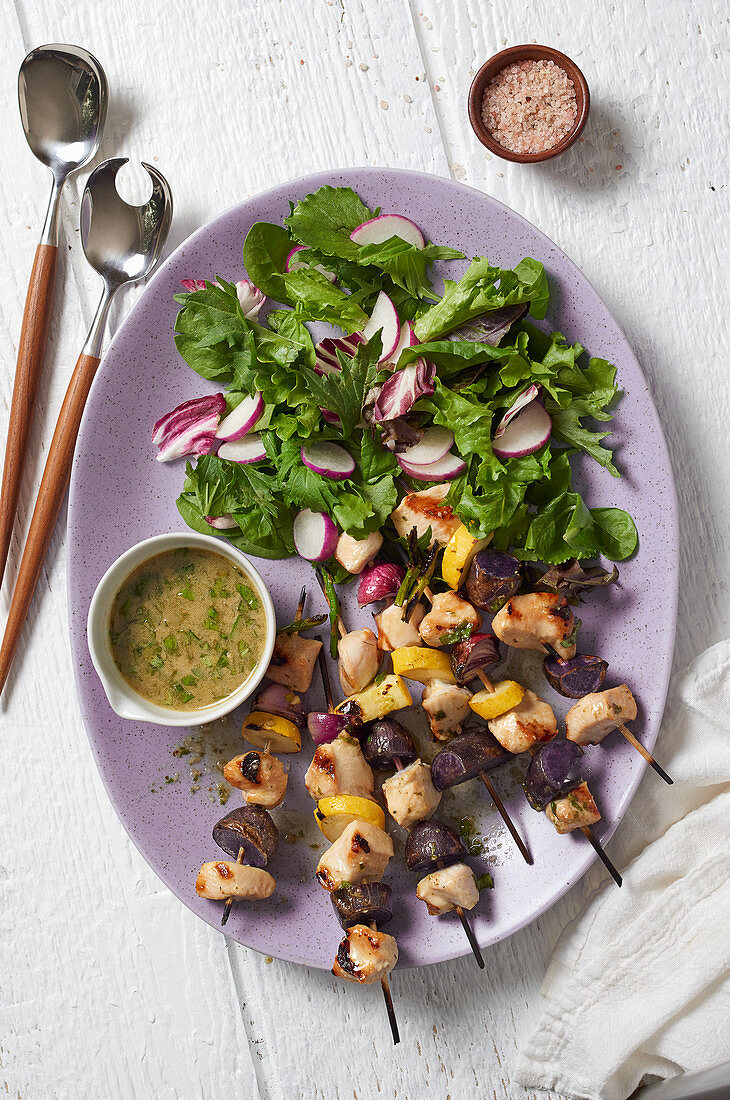 Chicken skewers with a side salad (seen from above)