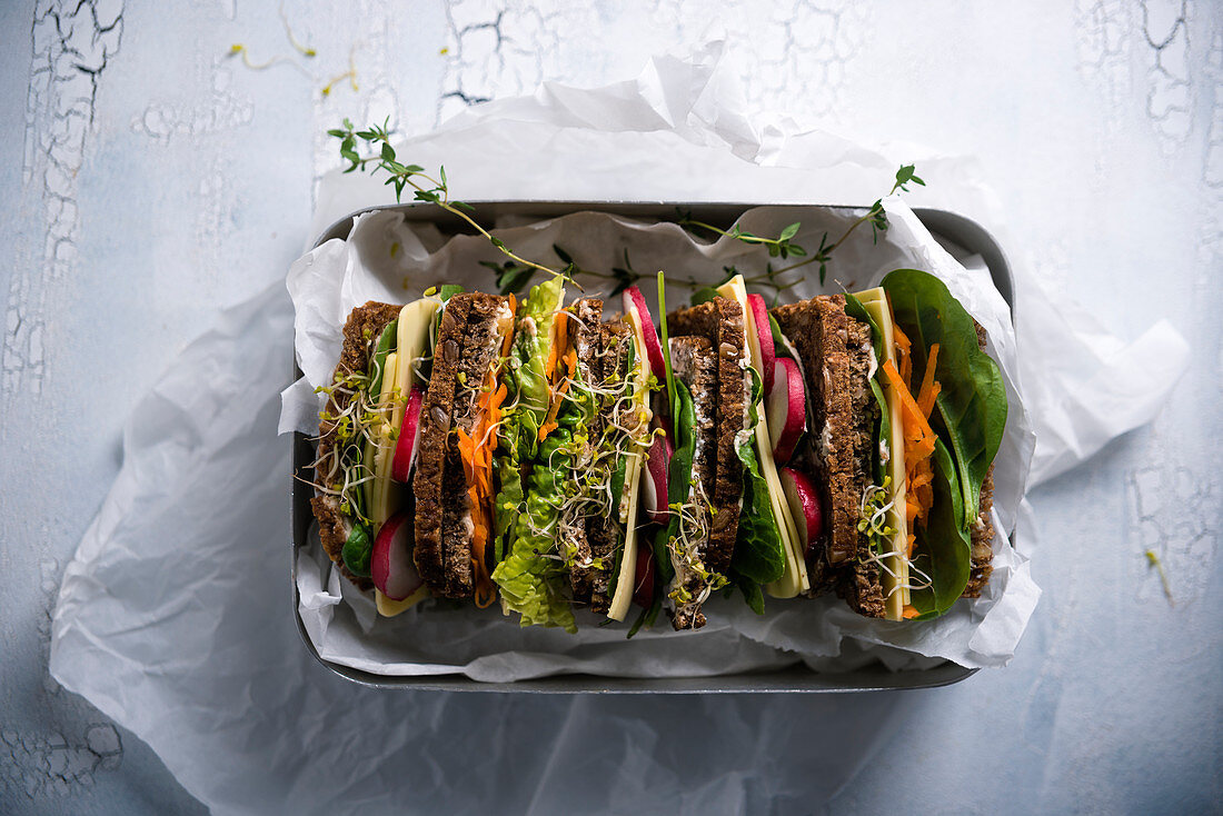 Colourful vegan wholemeal sandwiches with almond cheese in a lunchbox