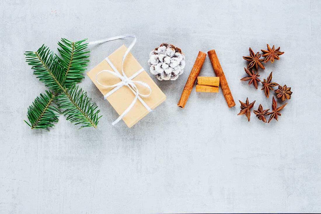 Christmas composition with gift box, cinnamon, anise star, pine cone and fir branches