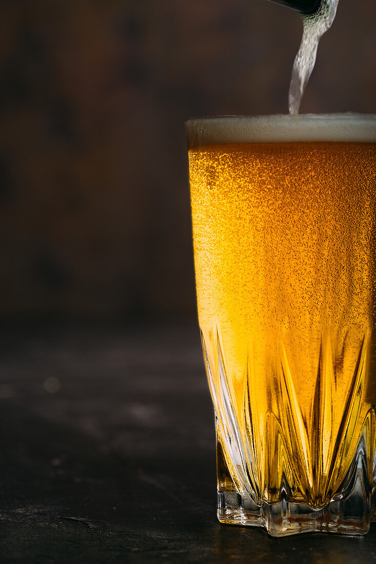 Pouring beer into a glass on dark background