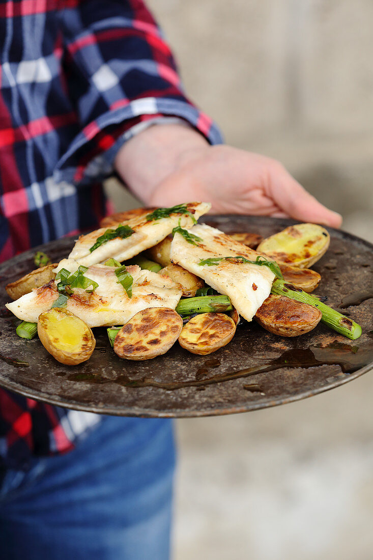 A man serving grilled catfish fillets with potatoes, green asparagus and wild garlic
