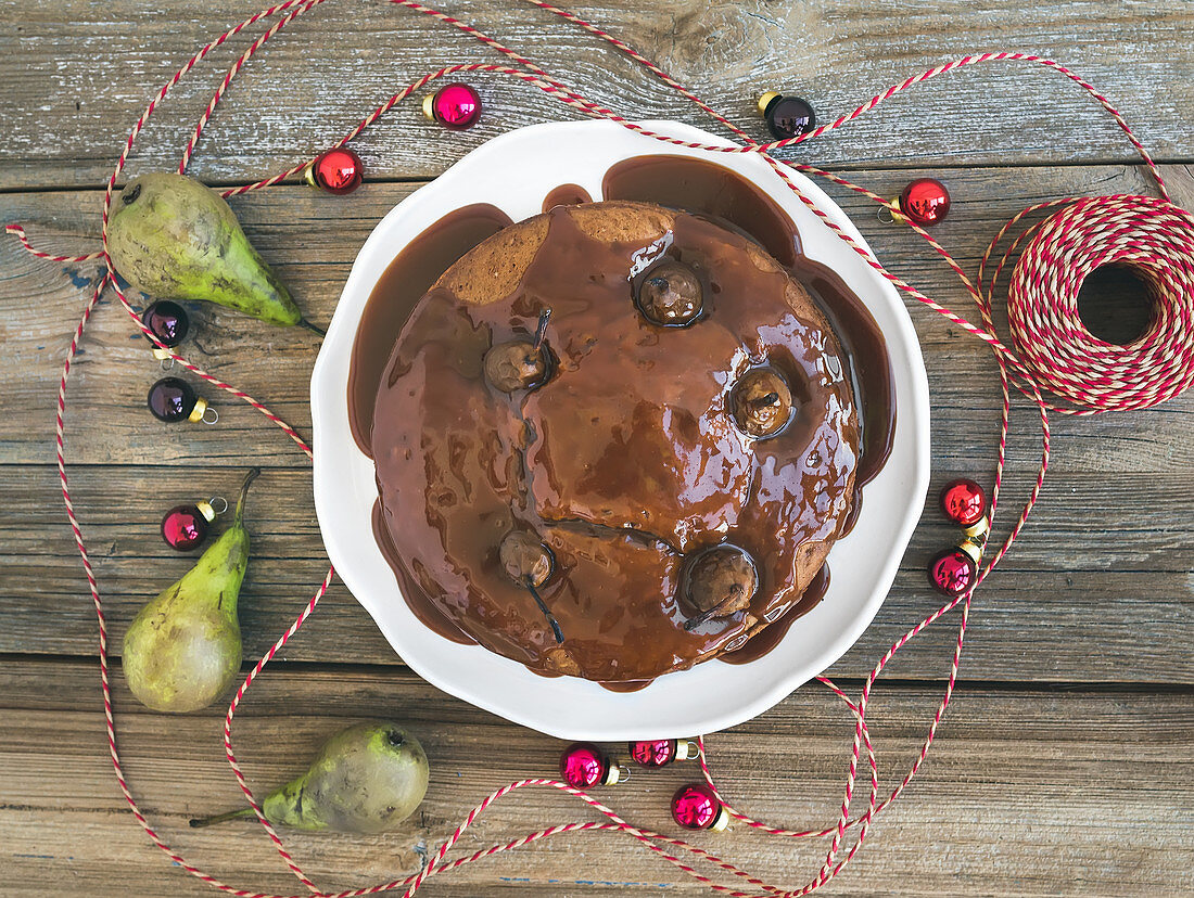 Christmas pear, ginger and honey cake with creamy caramel topping, fresh pears and Christmas decoration