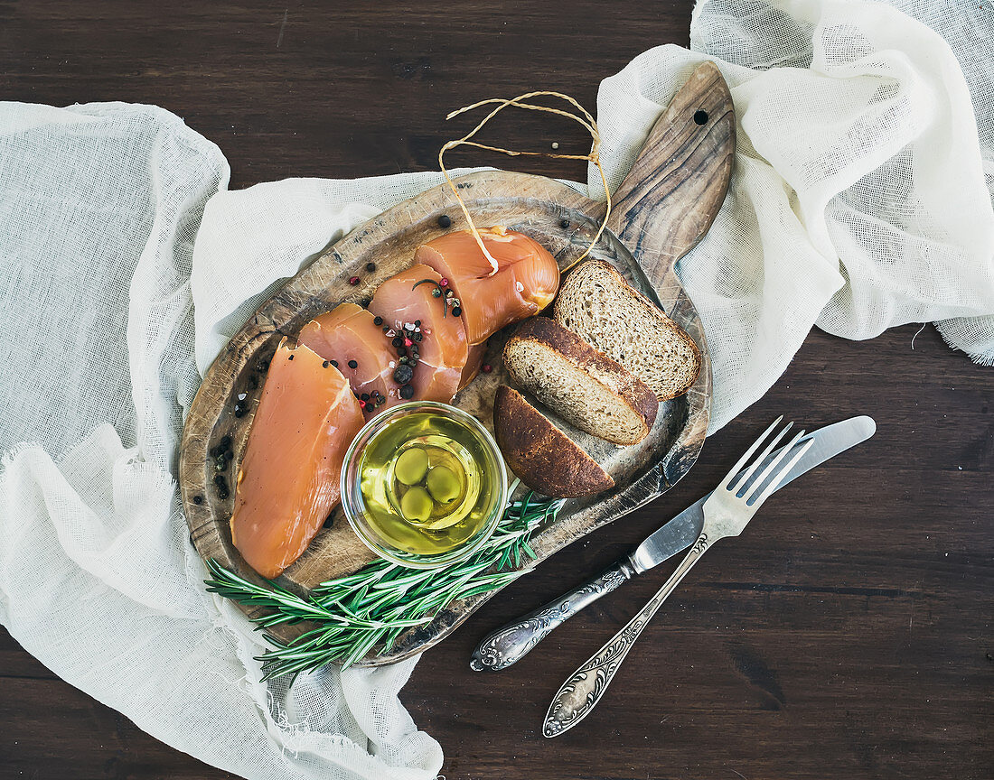 Smoked chicken, bread and olives on a wooden board