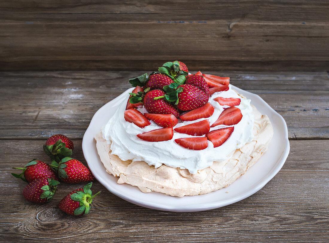 Rustic Pavlova cake with fresh strawberries and whipped cream
