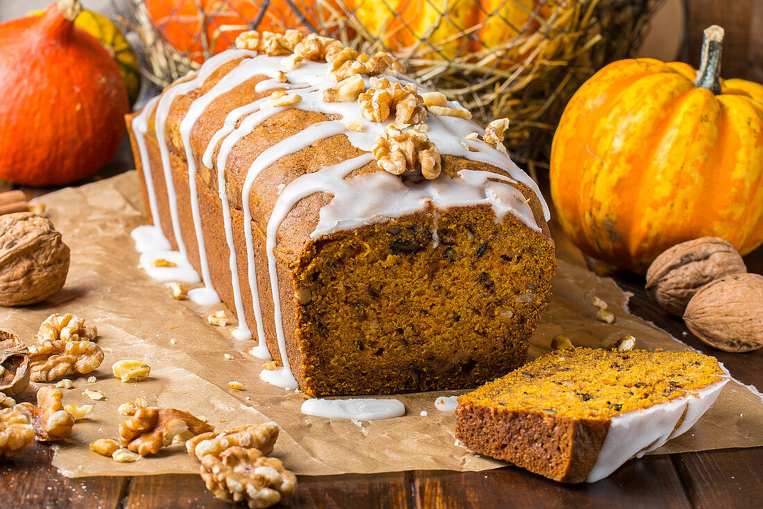 Pumpkin and walnut banana bread on baking paper with icing
