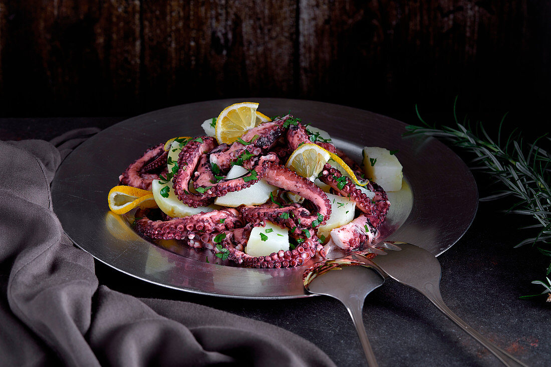 Octopus and potato salad on stainless plate