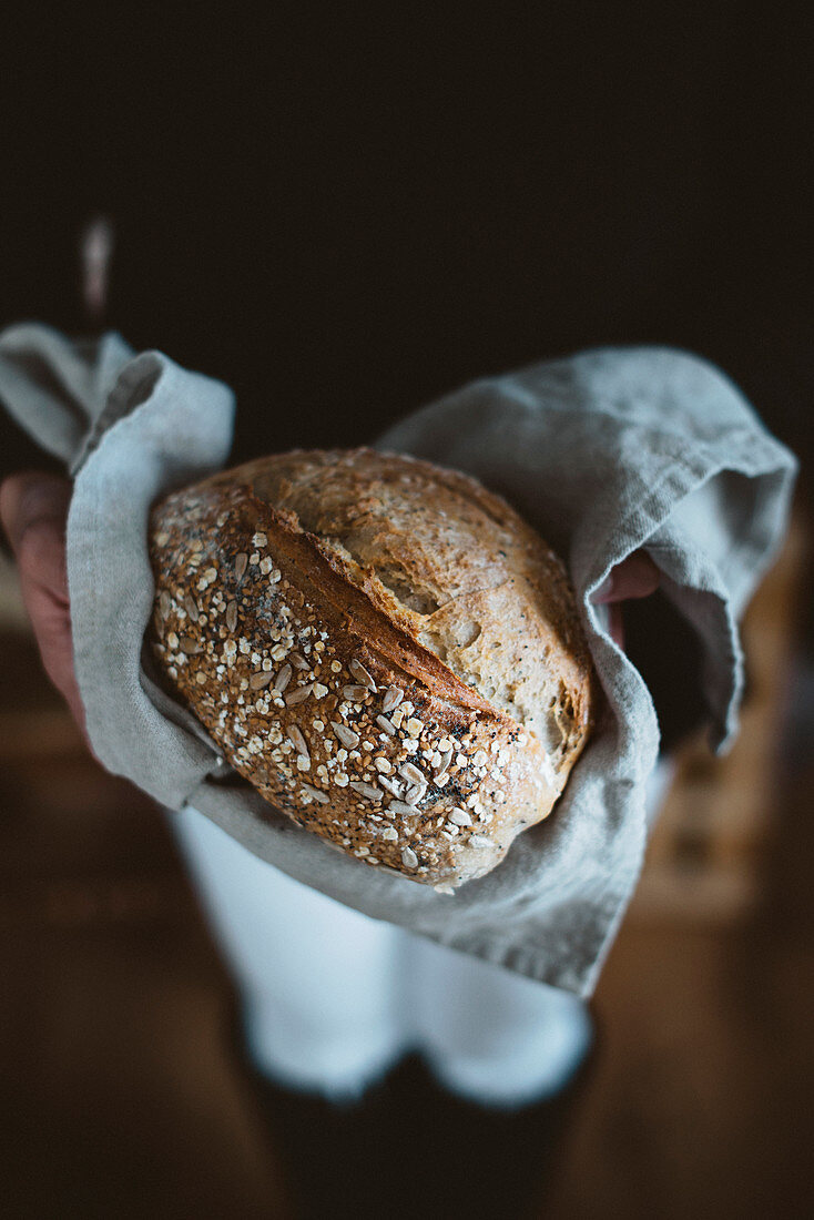 Person carrying loaf of fresh bread on dishcloth