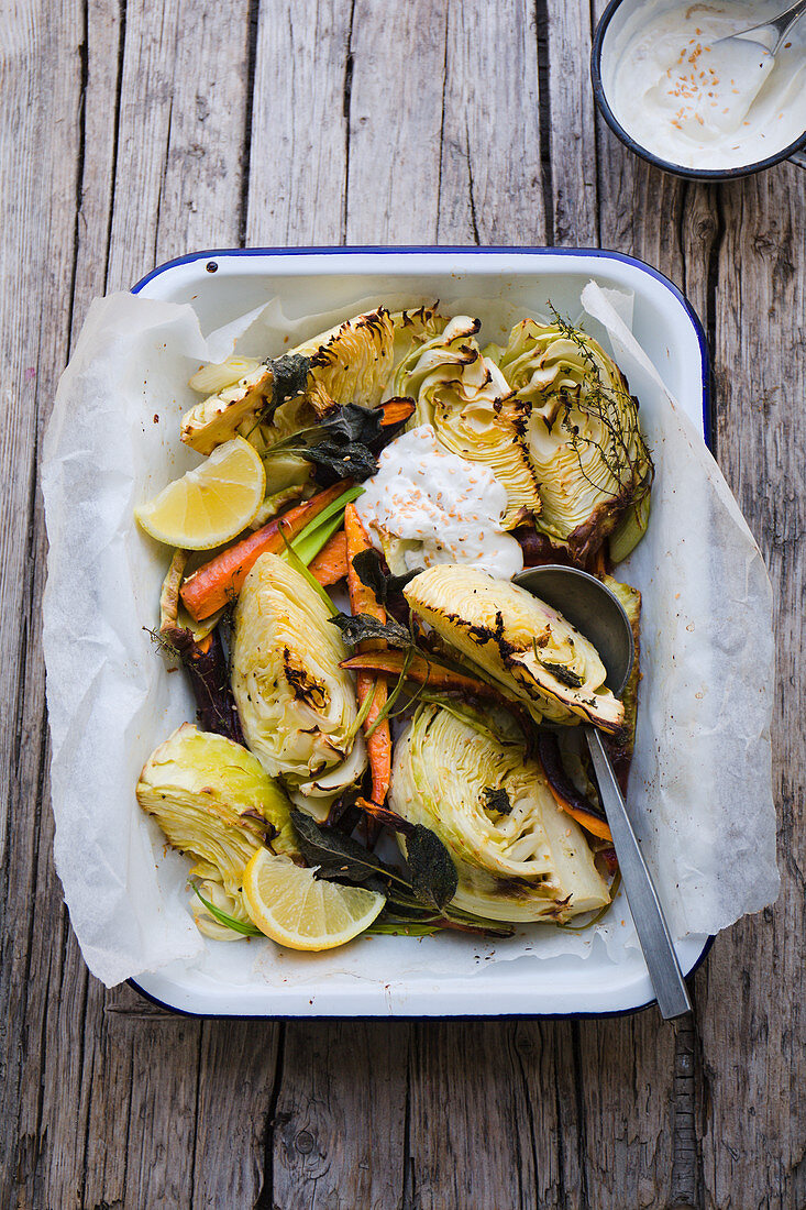 Roasted white cabbage in a baking dish with sage, carrots, lemon and a yoghurt dip
