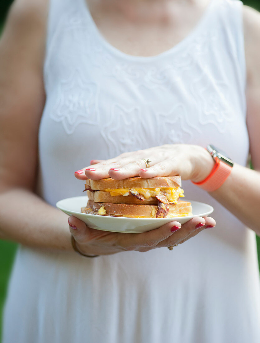 A woman holding a grilled cheese sandwich