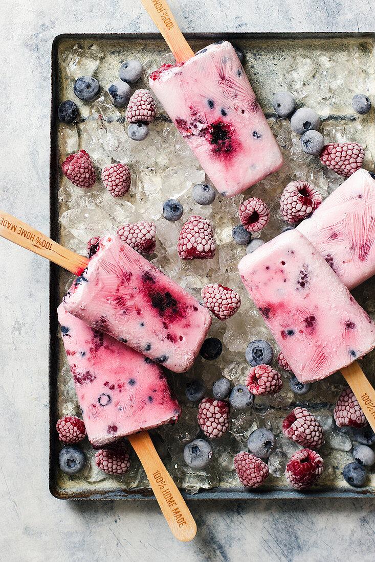 Homemade ice cream popsticles from yogurt, honey and berries, raspberries and blueberries on ice