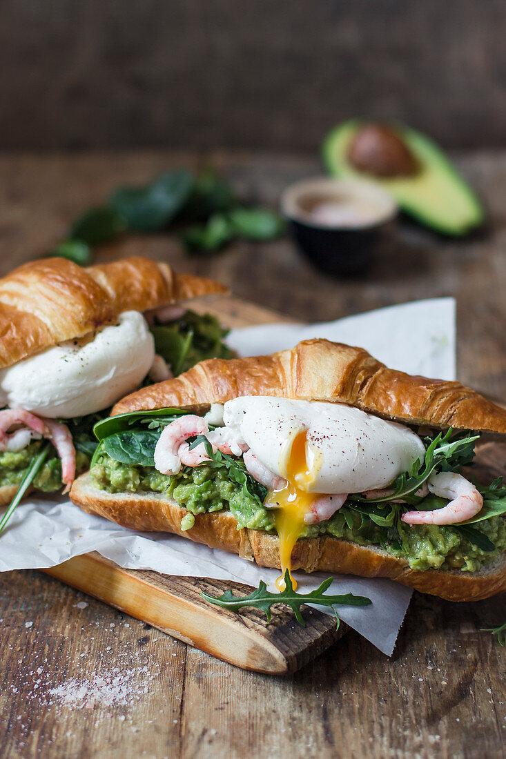 Croissant mit Avocadopüree, Garnelen, pochiertem Ei, Rucola und Spinat